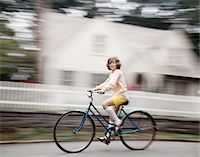 1970s BLURRED MOTION YOUNG GIRL IN YELLOW SHORTS WHITE KNEE SOCKS RIDING BLUE BIKE Stock Photo - Premium Rights-Managednull, Code: 846-05646718