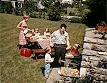 1960s FAMILY FATHER MOTHER TWO DAUGHTERS TWO SONS BACKYARD BAR-B-QUE OUTDOOR