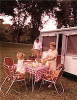1960s FAMILY RV CAMPING FATHER GRILLING MOTHER  AND GIRLS SETTING TABLE Stock Photo - Premium Rights-Managednull, Code: 846-05646760