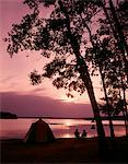 1960s SILHOUETTE OF COUPLE CAMPING BY LAKE AT SUNSET