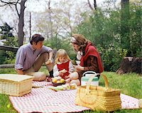 1960s - 1970s FAMILY MOTHER FATHER GIRL SPRING PICNIC ON CHECKERED TABLECLOTH Stock Photo - Premium Rights-Managednull, Code: 846-05646776