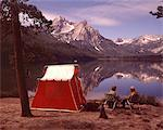 1970s OLDER COUPLE SITTING CAMPING BY RED TENT STANLEY LAKE IDAHO