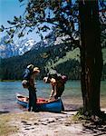 1970s COUPLE WITH FISHING GEAR CANOE BY STRING LAKE  GRAND TETON NATIONAL PARK WYOMING