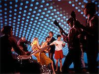 1960s - 1970s TEENAGERS DANCING AT DISCOTHEQUE WITH BAND PLAYING MUSIC BLUE LIGHTING EFFECTS Stock Photo - Premium Rights-Managednull, Code: 846-05646798
