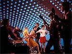 1960s - 1970s TEENAGERS DANCING AT DISCOTHEQUE WITH BAND PLAYING MUSIC BLUE LIGHTING EFFECTS