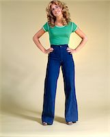 1970s SMILING YOUNG WOMAN WITH LONG BLOND CURLY HAIR STANDING HANDS ON HIPS IN BELL BOTTOM DENIM BLUE JEANS Stock Photo - Premium Rights-Managednull, Code: 846-05646989