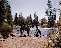 1970s COWBOY STANDING IN STREAM LEADING HORSE BY REINS TO WATER Stock Photo - Premium Rights-Managednull, Code: 846-05647017