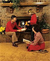sweater and fireplace - 1970s - 1980s FAMILY FATHER MOTHER DAUGHTER SITTING BY FIREPLACE POPPING CORN Stock Photo - Premium Rights-Managednull, Code: 846-05647085