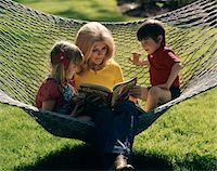 1970s MOTHER SON AND DAUGHTER SITTING IN HAMMOCK READING A BOOK OUTDOOR Stock Photo - Premium Rights-Managednull, Code: 846-05647140