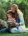 1970s MOTHER READING BOOK TO DAUGHTER IN GARDEN OUTDOOR