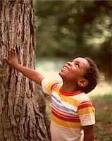 1970s SMILING AFRICAN-AMERICAN BOY LOOKING UP TREE TRUNK WEARING  STRIPED TEE SHIRT Stock Photo - Premium Rights-Managednull, Code: 846-05647161