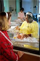 NURSE IN HOSPITAL NURSERY SHOWING BABY TO MOTHER THROUGH WINDOW Stock Photo - Premium Rights-Managednull, Code: 846-05647186