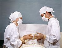 1950s - 1960s DOCTOR & NURSE IN SURGERY OPERATION OPERATING STERILE SURGICAL WHITE CAPS GOWNS MASKS Stock Photo - Premium Rights-Managednull, Code: 846-05647219