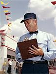 1950s - 1960s MAN SERVICE MANAGER AT AUTOMOBILE GAS AND REPAIR SERVICE STATION WRITING ON CLIPBOARD