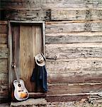 1960s - 1970s GUITAR, HAT AND JACKET HANGING BY WEATHERED LOG CABIN DOOR Stock Photo - Premium Rights-Managed, Artist: ClassicStock, Code: 846-05647245