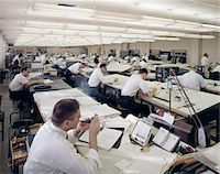 1960s OFFICE FULL OF DRAFTING TABLES DESIGNER MAN LIGHTING-UP A PIPE OF TOBACCO INDOOR INDUSTRY Stock Photo - Premium Rights-Managednull, Code: 846-05647270
