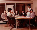 1970s BUSINESS MEETING SIX SERIOUS PEOPLE SITTING AROUND CONFERENCE TABLE