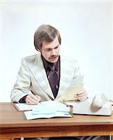 1970s BUSINESS MAN AT DESK HANDLING PAPERWORK OFFICE TELEPHONE Stock Photo - Premium Rights-Managednull, Code: 846-05647276