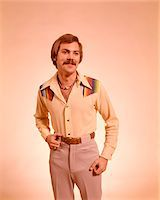 1970s FASHION STYLE YOUNG MAN PORTRAIT MUSTACHE NECKLACE CASUAL CLOTHES SHIRT PANTS Stock Photo - Premium Rights-Managednull, Code: 846-05647294