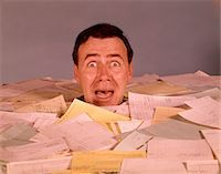 person overwhelmed stresss - 1960s OVERWHELMED SCREAMING BUG-EYED MAN OFFICE WORKER DROWNING IN PAPER WORK UP TO HIS NECK SURROUNDED BY BILLS AND INVOICES Stock Photo - Premium Rights-Managednull, Code: 846-05647314