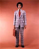 1970s PORTRAIT OF SMILING AFRICAN AMERICAN BUSINESSMAN SALESMAN IN GLEN PLAID SUIT AND TIE WITH AFRO HAIR STYLE HOLDING LEATHER BRIEFCASE Stock Photo - Premium Rights-Managednull, Code: 846-05647402