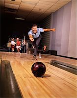 1960s SMILING MAN FATHER ROLLING BOWLING BALL DOWN ALLEY FAMILY WATCHING IN BACKGROUND Stock Photo - Premium Rights-Managednull, Code: 846-05647423