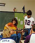 1980s COLLEGE STUDENTS IN CLASSROOM PLAYING GUITAR