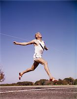 finish line - 1960s RUNNER AT FINISH LINE BREAKING THROUGH TAPE Stock Photo - Premium Rights-Managednull, Code: 846-05647441