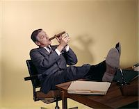 1960s SUCCESSFUL BUSINESSMAN WITH LOOK OF SATISFACTION SITTING WITH SHOES PROPPED ON DESK LIGHTING-UP A HUGE CIGAR Stock Photo - Premium Rights-Managednull, Code: 846-05647486