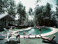 1950s FAMILY MAN WOMAN SON DAUGHTER BACKYARD KIDNEY SHAPE SWIMMING POOL PICNIC FOOD BEACH BALL HOUSE TREES SUMMER Stock Photo - Premium Rights-Managednull, Code: 846-05647505