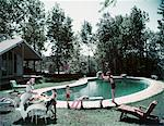 1950s FAMILY MAN WOMAN SON DAUGHTER BACKYARD KIDNEY SHAPE SWIMMING POOL PICNIC FOOD BEACH BALL HOUSE TREES SUMMER