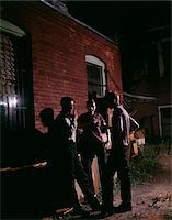 1950s - 1960s THREE TEENAGE BOYS LOITERING IN ALLEY AT NIGHT SMOKING CIGARETTES Stock Photo - Premium Rights-Managednull, Code: 846-05647567