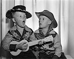 1950s 2 JUVENILE BOYS IN COWBOY HAT & SHIRTS PLAYING UKULELE & SINGING MOUTH OPEN WIDE Stock Photo - Premium Rights-Managed, Artist: ClassicStock, Code: 846-05647641