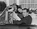 1950s HUSBAND WIFE MAN WOMAN IN AUTOMOBILE READING MAP