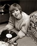 1960s SMILING YOUNG WOMAN SWEATER LYING ON BEDROOM FLOOR LISTENING TO MUSIC ON VINYL RECORD ALBUM Stock Photo - Premium Rights-Managed, Artist: ClassicStock, Code: 846-05647681
