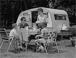1960s FAMILY CAMPING EATING MEAL BESIDE RV CAMPER