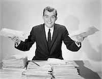 piles of work - 1950s AMUSED SMILING BUSINESSMAN HOLDING PAPERS FROM THE PILES ON HIS DESK Stock Photo - Premium Rights-Managednull, Code: 846-05647734