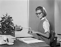 secretary desk - 1960s SECRETARY TYPIST WEARING STYLISH EYEGLASSES USING MANUAL TYPEWRITER AT DESK Stock Photo - Premium Rights-Managednull, Code: 846-05647750