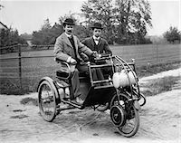 1900s TWO MEN IN BOWLER HATS SITTING IN THREE WHEEL MOTORIZED HORSELESS CARRIAGE EARLY AUTOMOBILE WITH TILLER STEERING Stock Photo - Premium Rights-Managednull, Code: 846-05647768