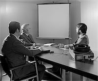 1970s THREE EXECUTIVE BUSINESSMEN CONFERENCE TABLE AUDIOVISUAL PRESENTATION Stock Photo - Premium Rights-Managednull, Code: 846-05647773