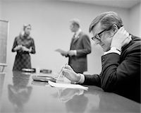 1970s WORRIED BUSINESSMAN SEATED CONFERENCE TABLE TWO PEOPLE IN BACKGROUND Stock Photo - Premium Rights-Managednull, Code: 846-05647777