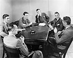 1930s - 1940s 6 BUSINESSMEN MEETING IN BOARDROOM AROUND TABLE WITH ASHTRAYS