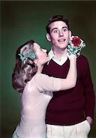 1940s - 1950s TEEN COUPLE GIRL HOLDING NOSEGAY BOUQUET HUGGING SURPRISED BOY LIPSTICK KISS ON CHEEK Stock Photo - Premium Rights-Managednull, Code: 846-05647818