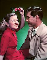 1950s SMILING TEEN COUPLE GIRL HOLDING CHRISTMAS MISTLETOE OVER HEAD Stock Photo - Premium Rights-Managednull, Code: 846-05647830