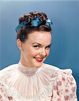 1940s - 1950s PORTRAIT SMILING WOMAN WEARING HIGH NECKED RUFFLED LACE BLOUSE BLUE RIBBON IN HAIR Stock Photo - Premium Rights-Managednull, Code: 846-05647869