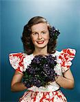 1940s - 1950s SMILING YOUNG WOMAN WEARING RED AND WHITE DRESS HOLDING BOUQUET OF VIOLETS