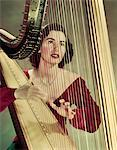 1940s - 1950s WOMAN PLAYING HARP WEARING RED VELVET GOWN Stock Photo - Premium Rights-Managed, Artist: ClassicStock, Code: 846-05647881