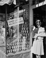 1940s WOMAN CARRYING PACKAGES IN DOOR OF NEW YORK CITY DELICATESSEN DISPLAYING A SIGN SANDWICHES TO TAKE OUT ARE NOT RATIONED Stock Photo - Premium Rights-Managednull, Code: 846-05647982
