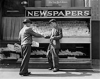 1940s MAN BUYING NEWSPAPER FROM VENDOR ON SIDEWALK NEW YORK CITY Stock Photo - Premium Rights-Managednull, Code: 846-05648003
