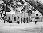1940s SERVICE STATION IN MOUNTAINS IN WINTER SEVERAL GAS PUMPS GARAGES & OIL & GAS SIGNS